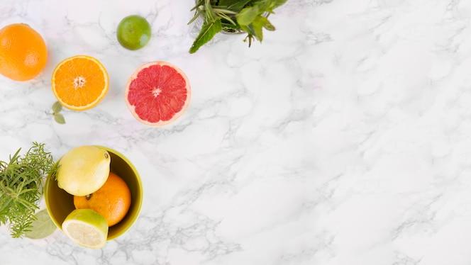 Vista elevada de frutas cítricas jugosas en mármol