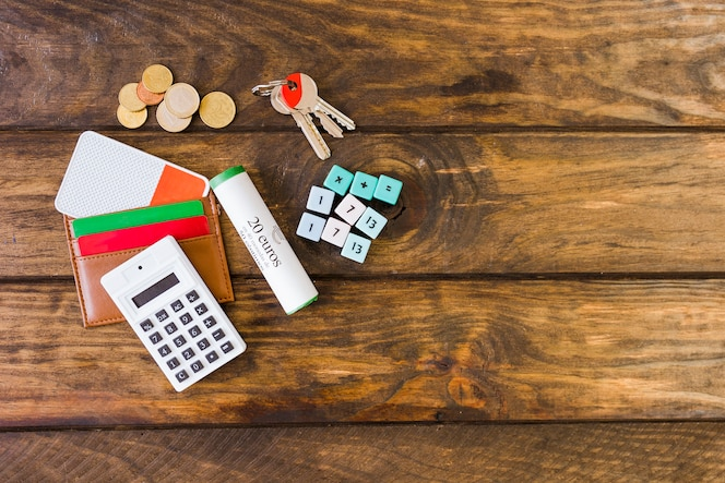 Vista elevada de la billetera con tarjetas, calculadora, bloques de matemáticas, llave y monedas en el escritorio