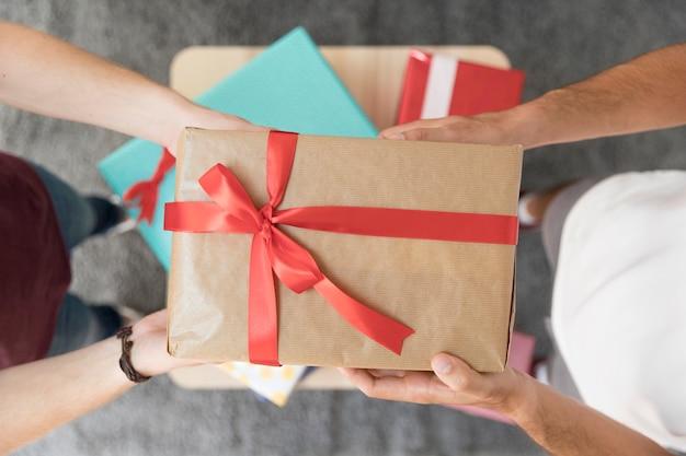 Vista elevada de la caja de regalo envuelta tenencia del amigo masculino con lazo de cinta roja
