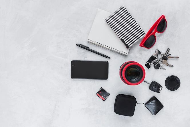 Vista elevada de la lente de la cámara, del cuaderno espiral, del teléfono móvil y de los accesorios personales en fondo