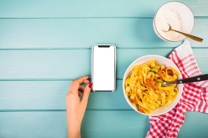 Vista elevada de la mano de la mujer cerca del teléfono inteligente y pasta tagliatelle