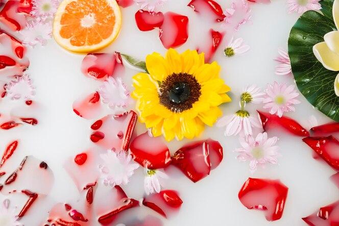 Vista elevada de leche con flor amarilla, pétalos y pomelo