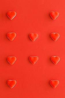 Vista elevada de los caramelos en forma de corazón en una fila en el contexto rojo