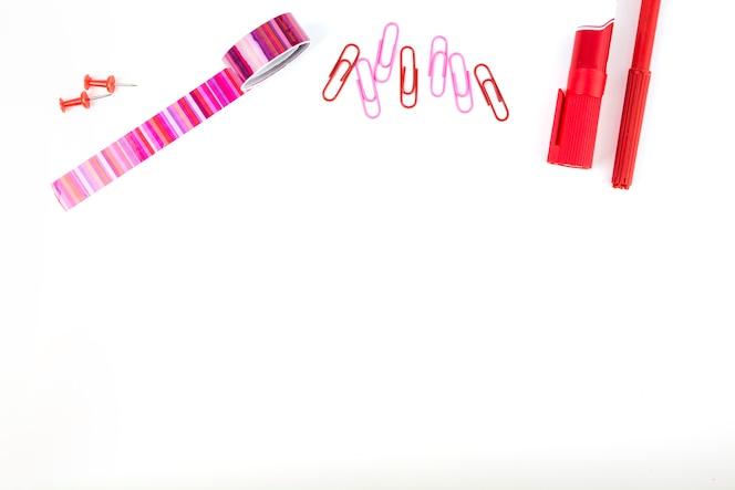 Vista elevada de los marcadores; clips de papel; cinta de violonchelo y marcadores sobre fondo blanco