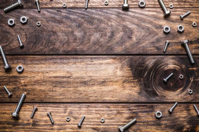 Vista elevada de pernos y tuercas en tablón de madera