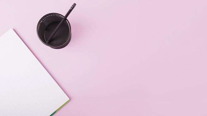 Vista elevada del portátil y vaso de plástico con lápiz sobre fondo rosa