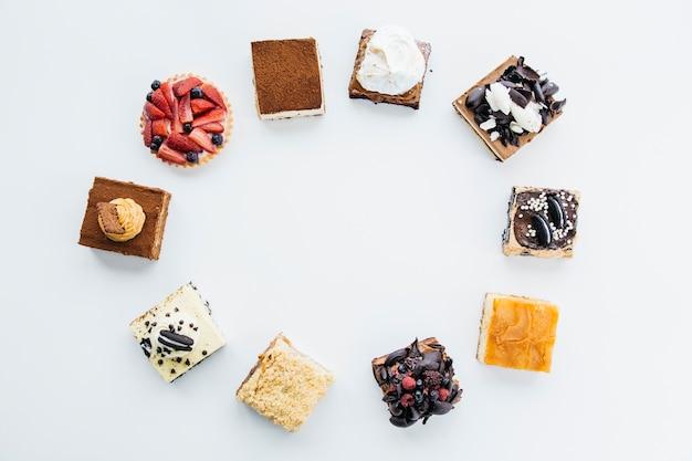 Vista elevada de deliciosos pasteles formando marco sobre fondo blanco