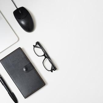 Vista elevada del diario; lente; bolígrafo; y portátil; ratón en mesa de oficina blanca