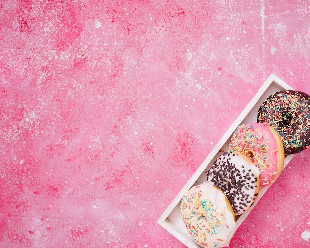 Una vista elevada de donuts en la caja de madera blanca en la esquina del fondo rosa