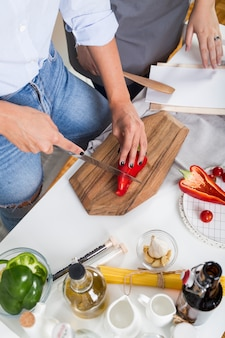 Vista elevada de dos mujeres preparando la comida en la cocina.