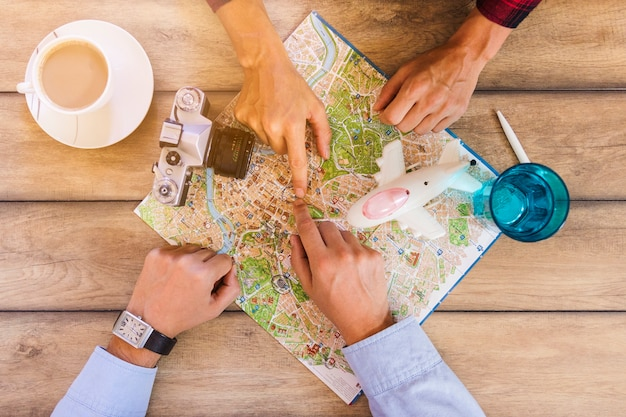 Vista elevada de dos personas que miran el mapa con una taza de té en el escritorio de madera