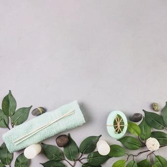 Vista elevada de dos toallas; hojas; jabón; spa piedras y velas en superficie gris