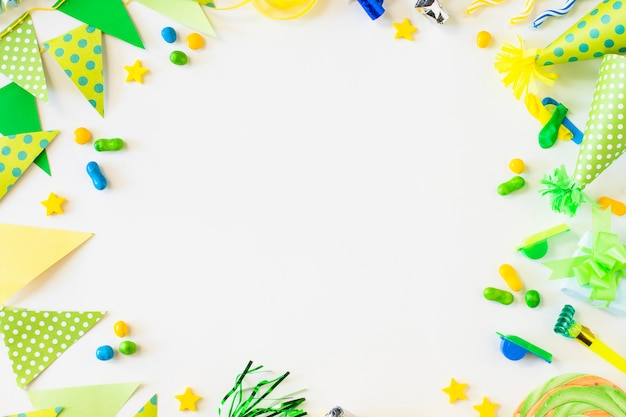 Vista elevada del empavesado; golosinas; soplador de cuerno de fiesta; silbato y sombrero en superficie blanca