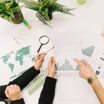 Vista elevada de empresarios analizando gráfico sobre escritorio
