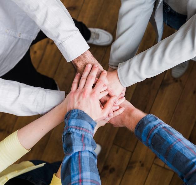 Vista elevada de empresarios apilando las manos unos sobre otros