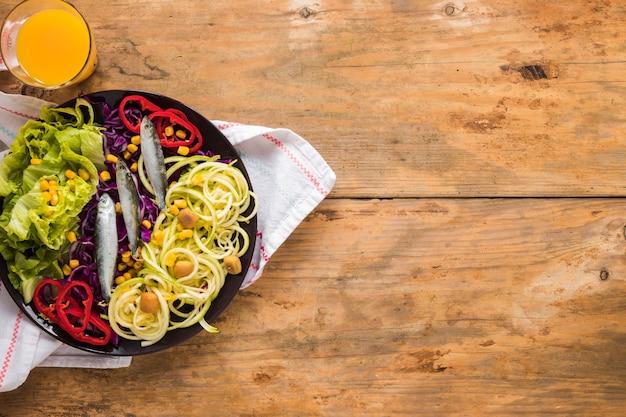 Vista elevada de ensalada fresca con pescado crudo; jugo y servilleta en mesa de madera