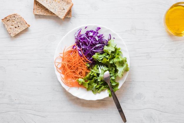 Vista elevada de ensalada saludable con tenedor; aceite y pan rebanadas contra escritorio de madera.