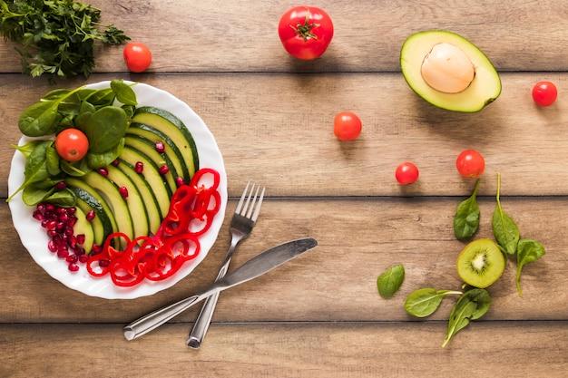 Vista elevada de una ensalada saludable de verduras y frutas en un plato blanco sobre una mesa de madera