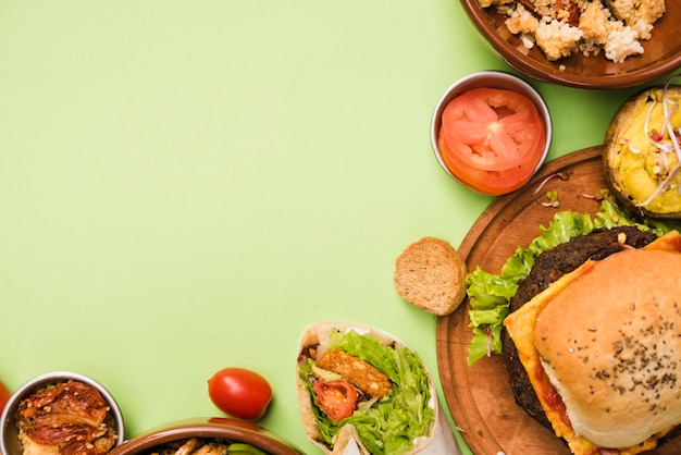 Una vista elevada de la envoltura de burrito; ensalada y hamburguesa sobre fondo verde