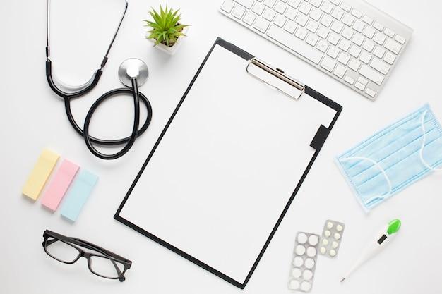 Vista elevada del escritorio del médico con portapapeles y teclado inalámbrico