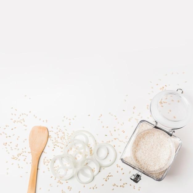 Vista elevada de la espátula; aros de cebolla y el tarro de arroz sobre fondo blanco