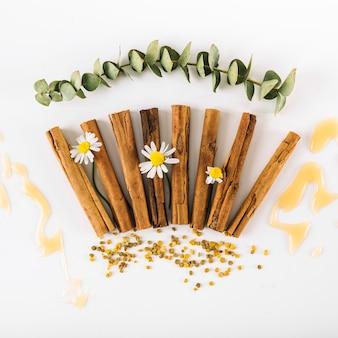 Vista elevada de las especias; flores; polen de miel y abeja sobre superficie blanca.