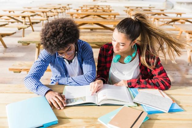 Una vista elevada de estudiantes universitarios leyendo los libros en el aula.