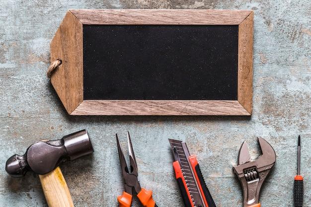 Vista elevada de la etiqueta de madera en blanco y varias herramientas de trabajo sobre fondo de madera vieja
