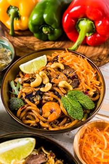 Una vista elevada de fideos udon con nueces; brócoli; menta; limón y camarones