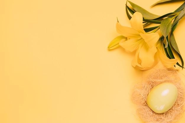 Una vista elevada de la flor de lirio fresco con huevo de pascua en el nido sobre fondo amarillo