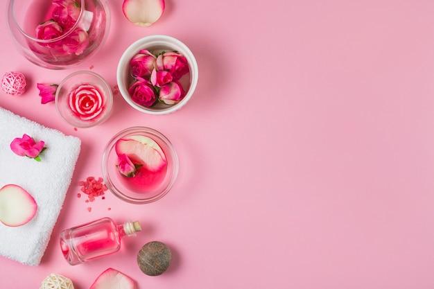 Vista elevada de las flores; aceite esencial; piedras de spa y toalla sobre fondo rosa