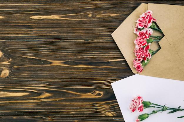 Vista elevada de flores de clavel en envuelve en mesa marrón