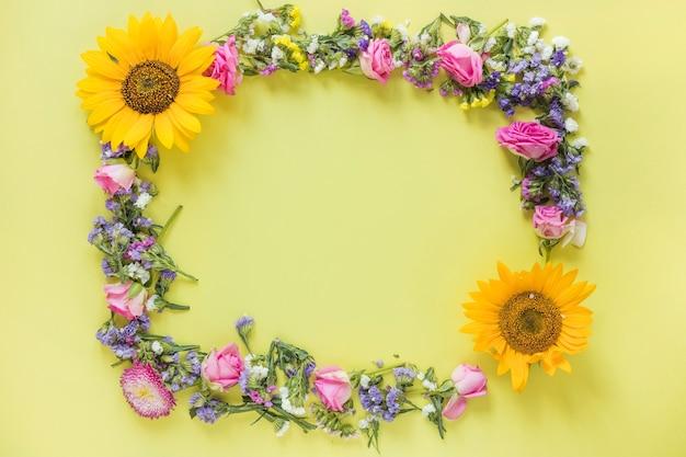 Vista elevada de flores frescas formando marco en superficie amarilla