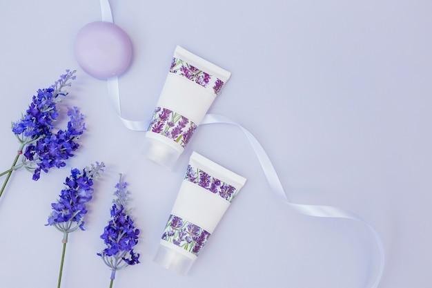 Vista elevada de flores de lavanda falsas; jabón; crema hidratante y cinta