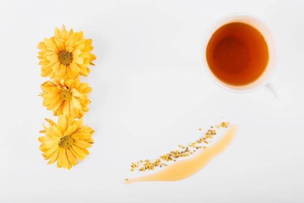 Vista elevada de flores; miel; polen de abeja y té en superficie blanca