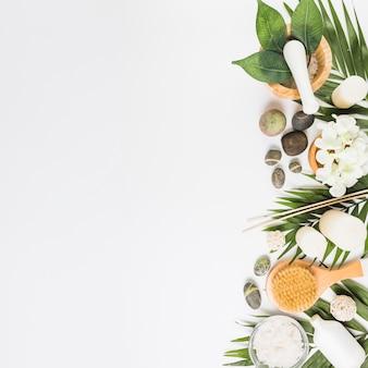 Vista elevada de las flores; piedras de spa; hojas; pincel y velas sobre fondo blanco