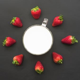 Vista elevada de fresas y leche sobre fondo negro