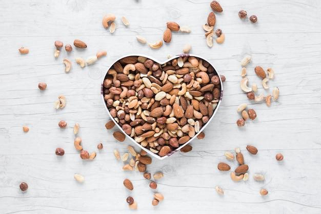 Vista elevada de frutos secos en forma de corazón contra el escritorio de madera