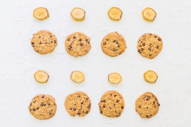Vista elevada de galletas y rodajas de banana en una fila