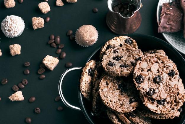 Una vista elevada de galletas en utensilios y granos de café sobre fondo negro