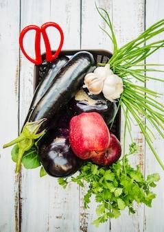Vista elevada de una granja de verduras y frutas frescas en una cesta sobre una mesa de madera