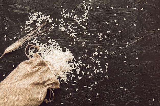 Vista elevada de granos de arroz crudos derramando de bolsa de yute sobre fondo gris