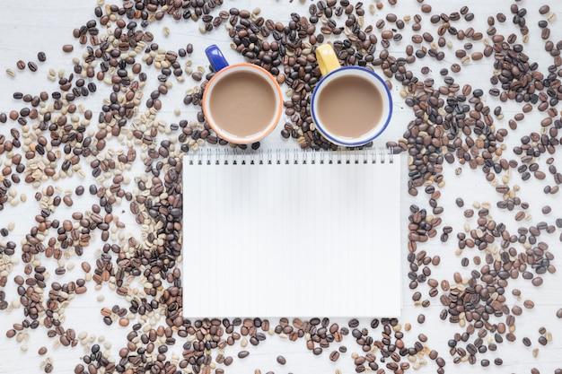 Vista elevada de los granos de café y la taza de café con libro espiral en blanco