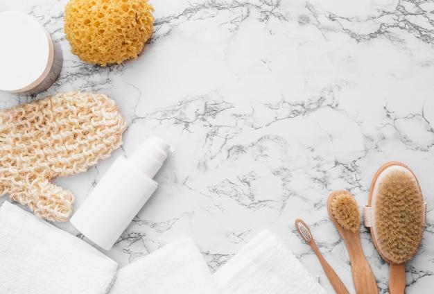 Vista elevada de guante de matorral; esponja; cepillo; toalla y crema hidratante sobre fondo de mármol.