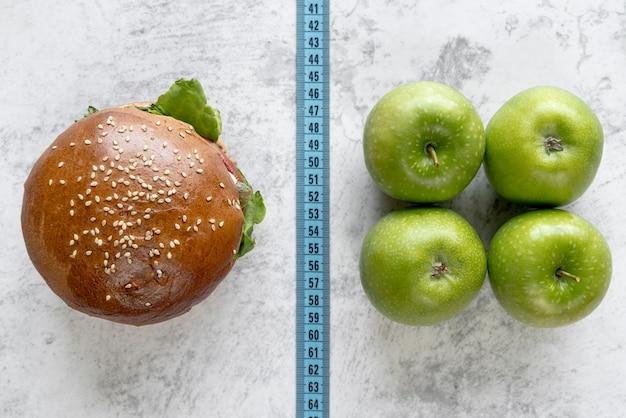 Vista elevada de la hamburguesa y la manzana en comparación con la cinta métrica
