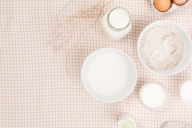 Vista elevada de la harina; leche; azucar y huevo sobre servilleta a cuadros
