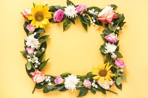 Vista elevada de hermosas flores frescas que forman el marco sobre fondo amarillo