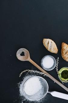 Vista elevada de hojaldre; harina; azúcar; petróleo; granos y utensilios sobre superficie negra.