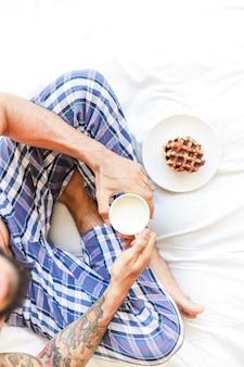 Vista elevada del hombre con una taza de leche y waffle sentado en la cama