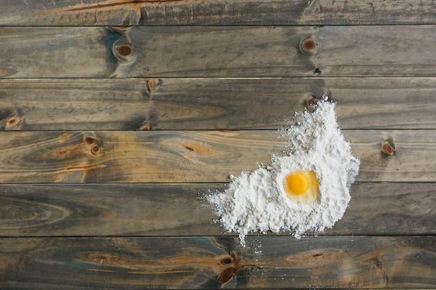 Vista elevada de huevo y harina sobre superficie de madera.